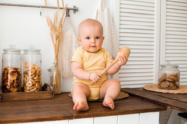家の木製キッチンに座っているかわいい幼児