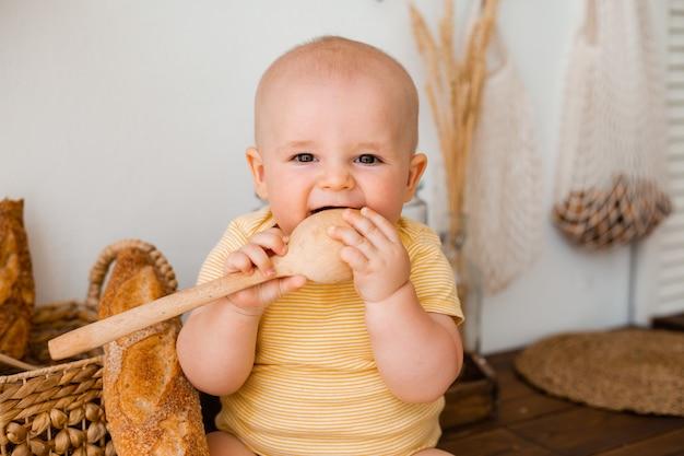 Милый малыш сидит на деревянной кухне дома