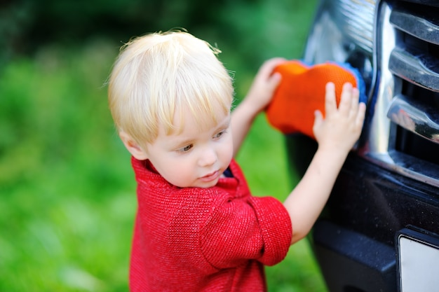 Cute toddler son playing washing fathers's car outdoors