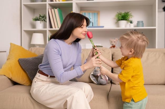 Милый малыш стоит на диване и дарит тюльпан матери, которая нюхает цветок с закрытыми глазами