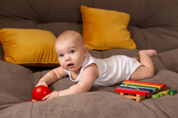 Cute toddler in white bodysuit lies at home on grey sofa with yellow pillows playing with wooden developing toy