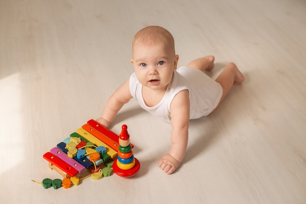 Cute toddler in white bodysuit lies on the wooden floor of the house with a developing toy