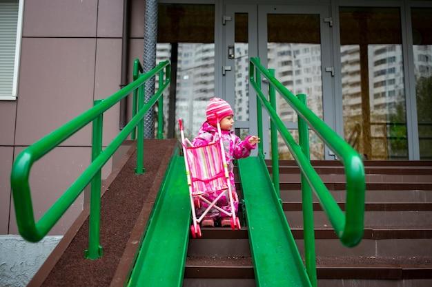 장난감 유모차가 있는 귀여운 유아가 휠체어 카트와 유모차를 위한 강철 난간 경사로를 따라 걷습니다.