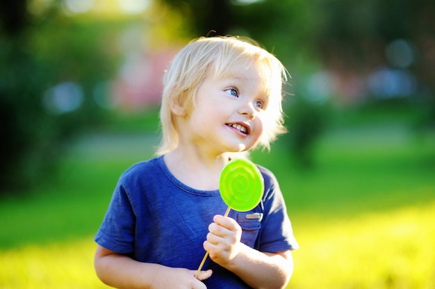 Cute toddler with big green lollipop. child eating sweet candy bar. sweets for young kids. summer outdoor fun