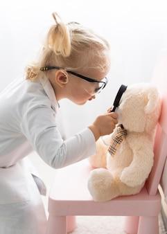 Милый малыш в защитных очках держит увеличительное стекло перед плюшевым мишкой