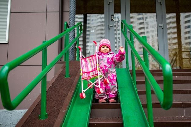 Cute toddler with a toy stroller walks along steel railing ramp for wheelchair carts and strollers