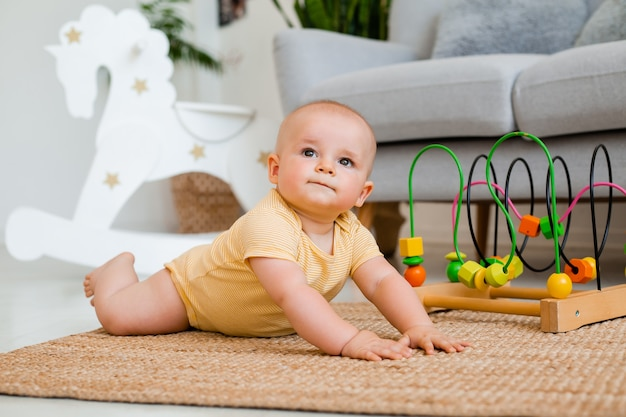 Cute toddler in yellow bodysuit sits at home on the floor playing in a developing toy. child development concept