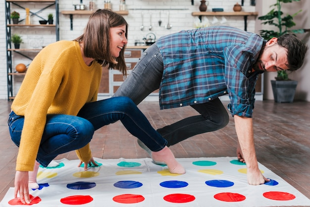 Cute toddlers playing in twister game at home