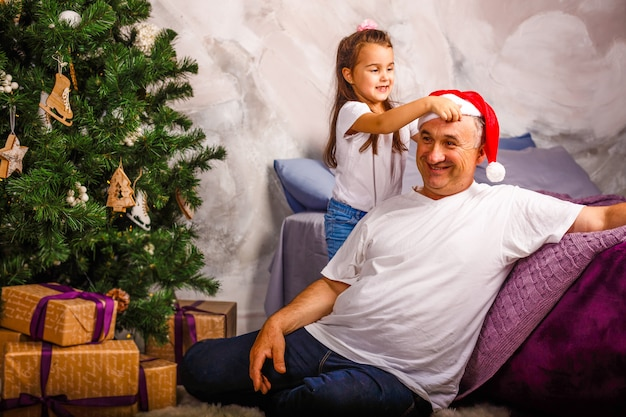 Cute toothless little girl and her grandfather decorating a christmas tree at home
