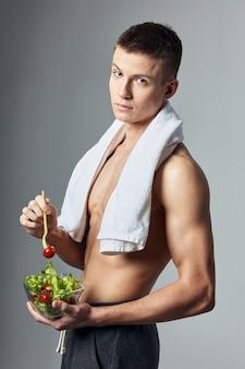 サラダの彼の肩のプレート上のかわいいトップレスの男のタオル