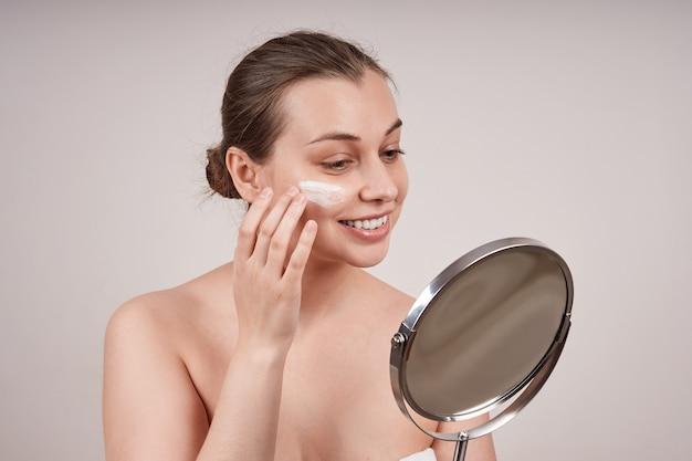 鏡を見ながら彼女の顔に栄養クリームを適用するかわいいトップレスの笑顔の若い女性は、灰色の壁に隔離します。