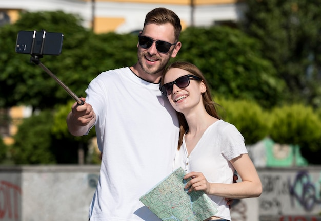 Cute tourist couple holding map and taking selfie