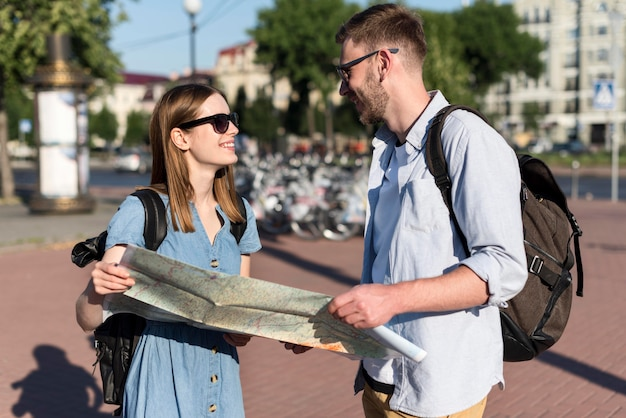 一緒に地図を保持しているかわいい観光客カップル