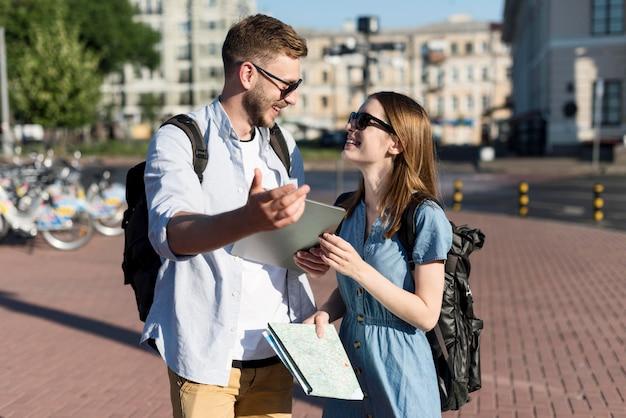 Милая туристическая пара, держа планшет и карту