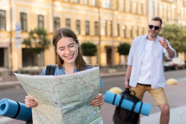 Милая туристическая пара позирует с картой и рюкзаком