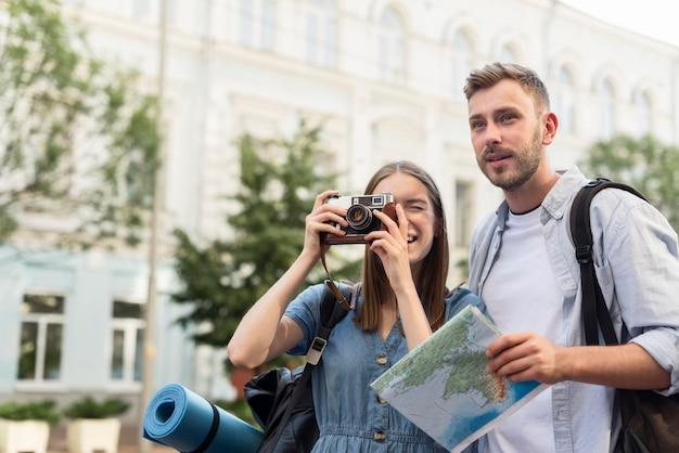 カメラで写真を撮るかわいい観光客カップル