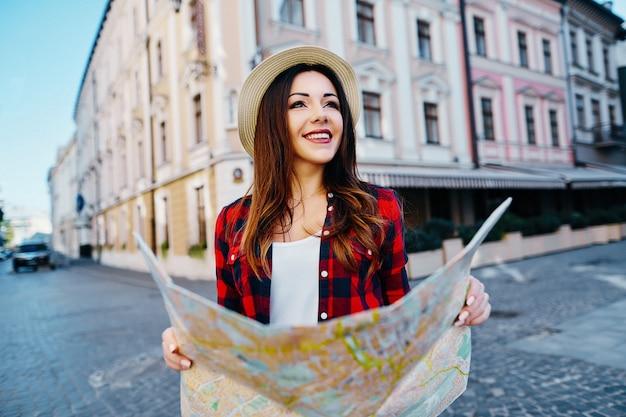 Милая туристическая девушка с каштановыми волосами в шляпе и красной рубашке, держа карту на фоне старого европейского города и улыбаясь, путешествуя, портрет.