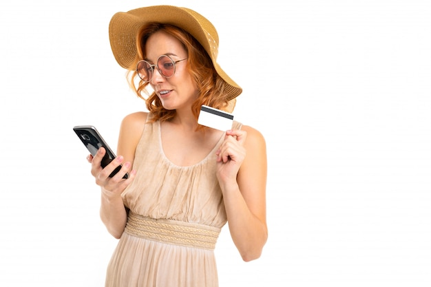 Cute tourist in a hat dressed in a summer dress and sunglasses orders tickets by phone and holds a credit card with a mockup on a white wall with blank space