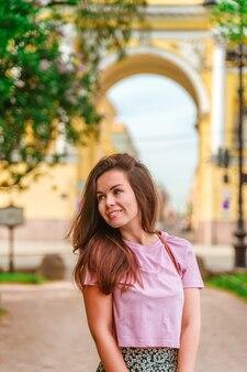 Милая туристическая женщина в санкт-петербурге на фоне желтой арки с красивой архитектурой туристического летнего сезона