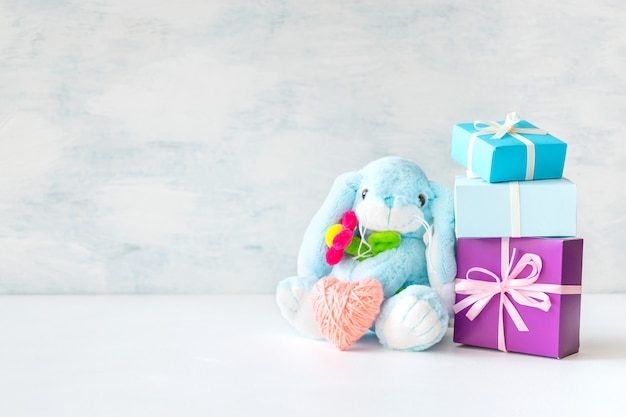 Cute toy soft bunny with flower, pink heart, gift boxes and soap bubbles