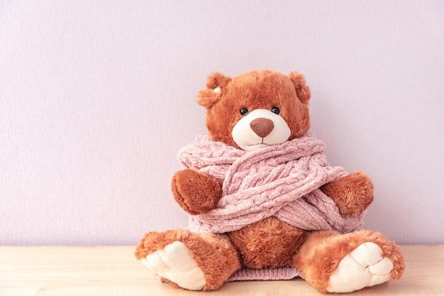 Милый игрушечный мишка в розовом вязаном свитере, сидя на полке дома.