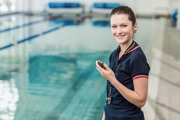 Cute trainer holding stopwatch at the pool