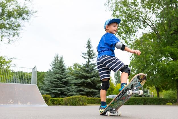 スケートパークで自分のスキルを披露しながら、空中に浮かび上がるフロントとバランスをとるスケートボードのかわいいトレンディな男の子