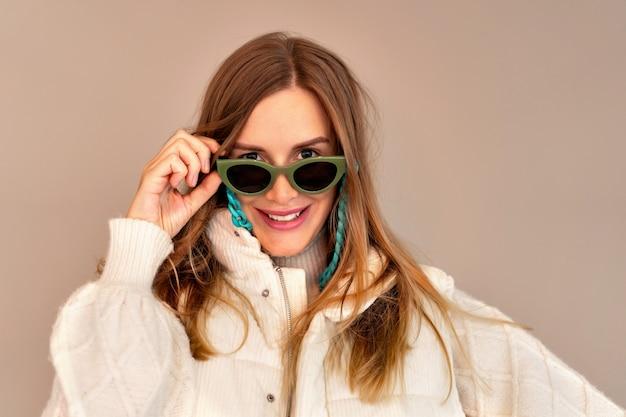 Симпатичный модный портрет стильной блондинки, позирующей на бежевой стене, в ярких солнцезащитных очках, свитере и жилете
