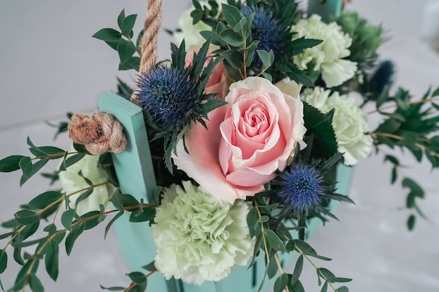 Cute turquoise-colored basket with a bouquet. long-playing bouquet in the style of boho.