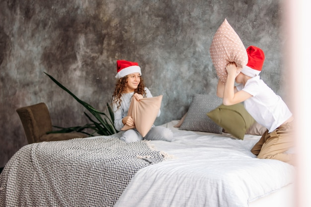 Cute tween children in santa hats and pajamas playing on bed with pillow, christmas morning time, kids party