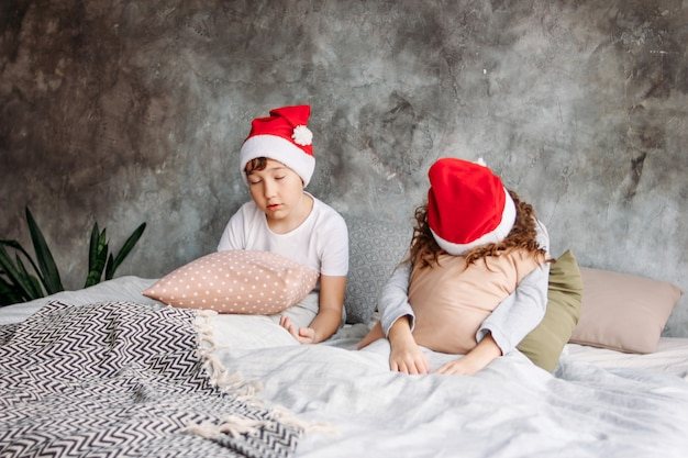 Cute tween children in santa hats don't want to wake up on bed with pillow in loft bedroom, christmas morning time
