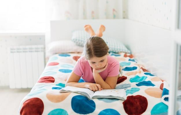 Милая девочка-подросток в розовой футболке читает книгу, лежа на кровати в светлой комнате дома