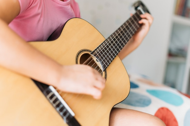 Cute tween girl in pink t-shirt play the guitar sit on bed in bright room at home, close up