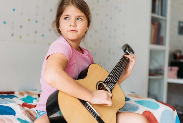 Cute tween girl in pink t-shirt play the guitar sit on bed in bright room at home