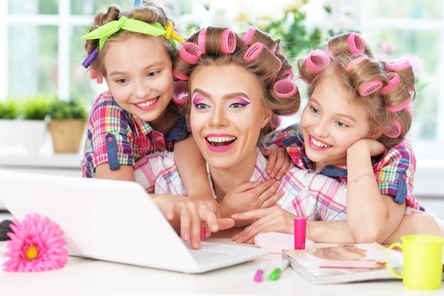 自宅でラップトップとヘアカーラーでかわいいトゥイニーの女の子と母親