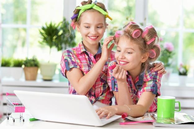 自宅でラップトップとヘアカーラーのかわいいトゥイニーの女の子