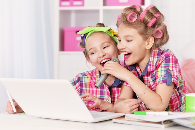 ノートパソコンでヘアカーラーのかわいいトゥイニーの女の子、自宅でカラオケで歌う