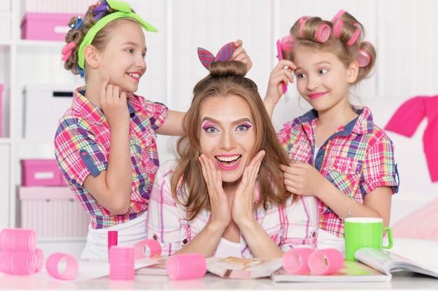 彼らの母親のために髪型をしているヘアカーラーで母親と一緒にかわいいトゥイニーの女の子