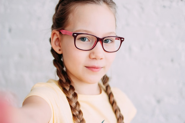 Cute tweens girl in yellow t-shirt with funny pigtails taking selfie on frontal camera