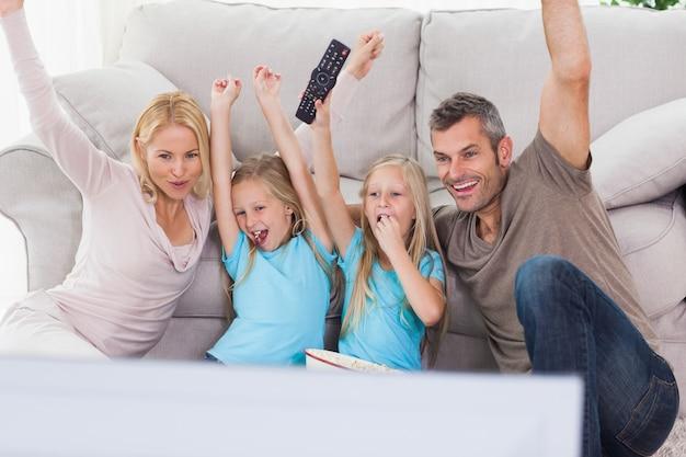 Симпатичные близнецы и родители, поднимающие оружие во время просмотра телевизора