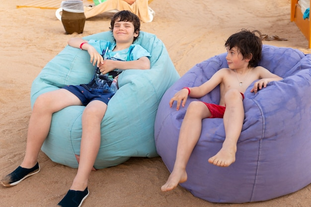 Cute two boys are sitting on the beach bean bag multicolored chairs at relaxing zone in a tropical resort.