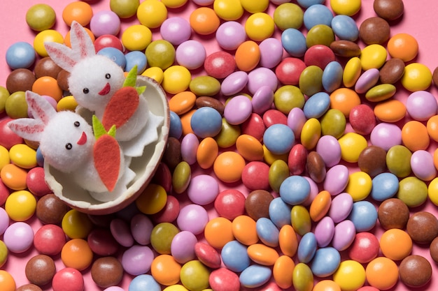 Cute two bunnies inside the broken easter egg over the colorful gem candies