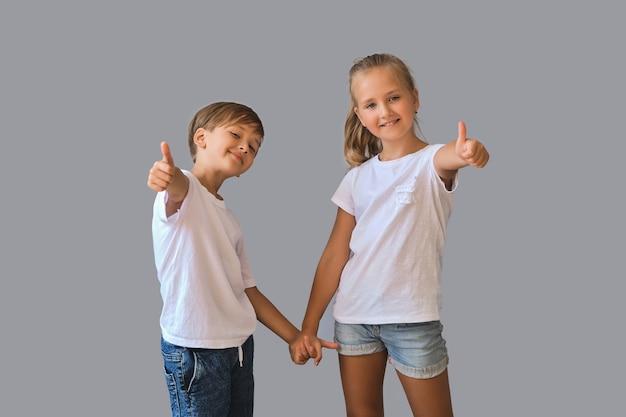 Симпатичные двое детей, маленький мальчик и девочка в белых футболках показывают большие пальцы в воздухе, рекомендуют, держатся за руки лучших друзей, изолированных на сером фоне