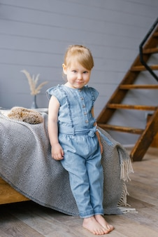 A cute two-year-old girl in a denim jumpsuit with bare feet stands by the bed at home