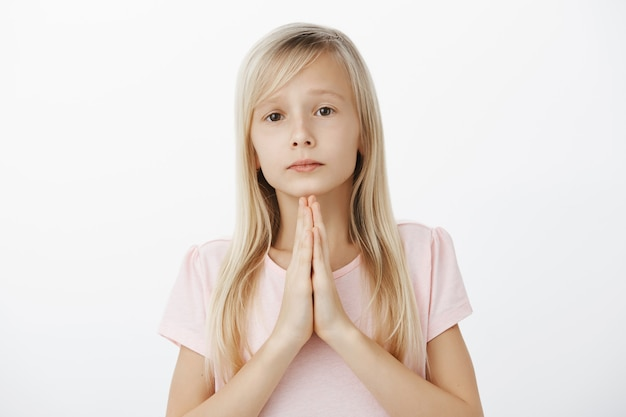 Cute upset girl begging and apologizing. portrait of serious moody blond daughter in adorable outfit, holding hands in pray with clenched palms, hoping for forgiveness over gray wall