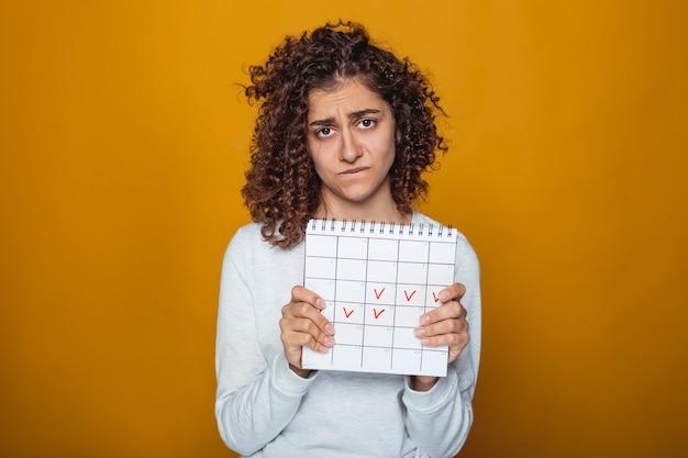 マークされた日とカレンダーを保持しているかわいい動揺インドの女の子