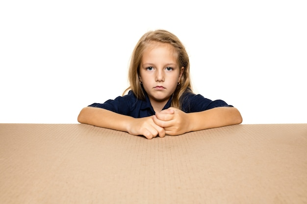 Cute and upset little girl opening the biggest package. disappointed young female model on top of cardboard box