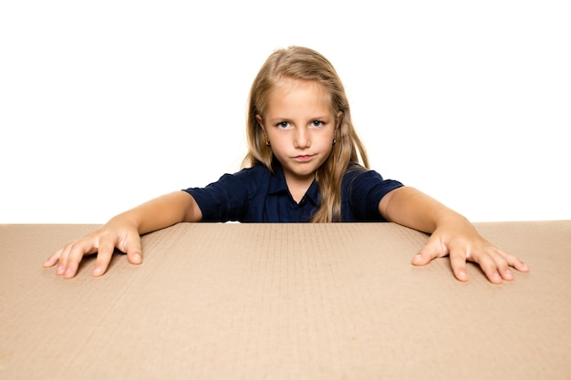 Cute and upset little girl opening the biggest postal package. disappointed young female model on top of cardboard box