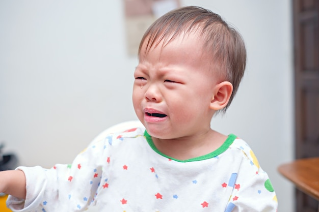 Cute upset stress sad unhappy little asian 2 years old toddler baby boy child crying