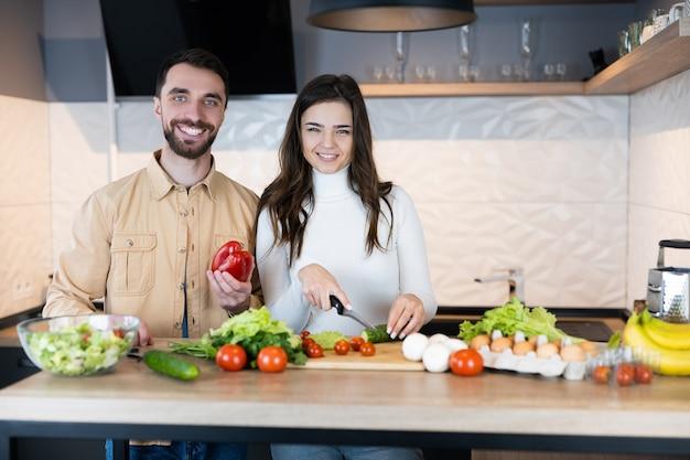 귀여운 채식 부부는 함께 요리하는 동안 웃고 있으며 너무 행복하고 건강 해 보입니다.